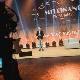 Philip Maderthaner auf einer Bühne mit Kameramann-Silhouette
