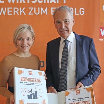 Zwei Personen in Kamera blickend vor Junge-Wirtschaft-Banner