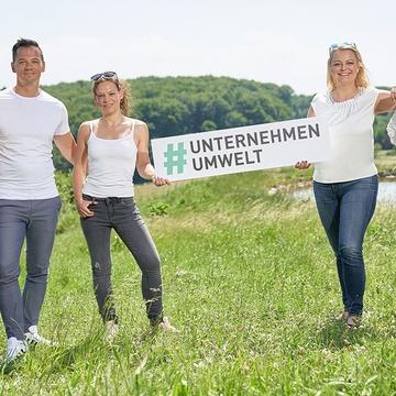 JW Team im Grünen mit Banner #unternehmenumwelt
