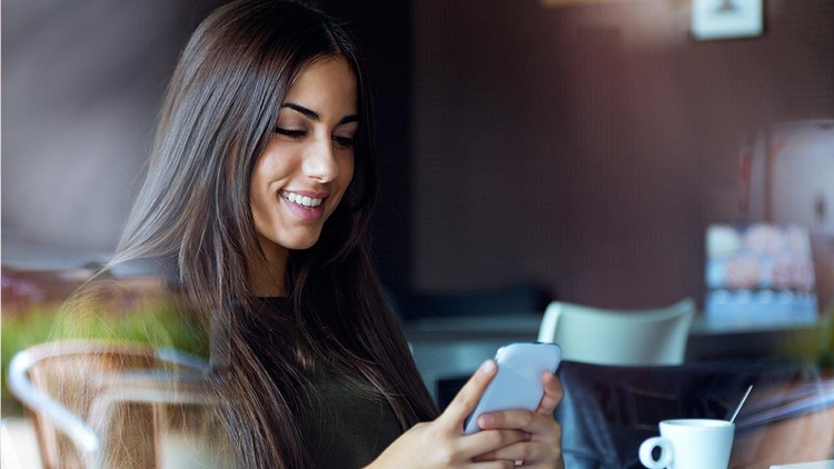 junge Frau tippt in Smartphone
