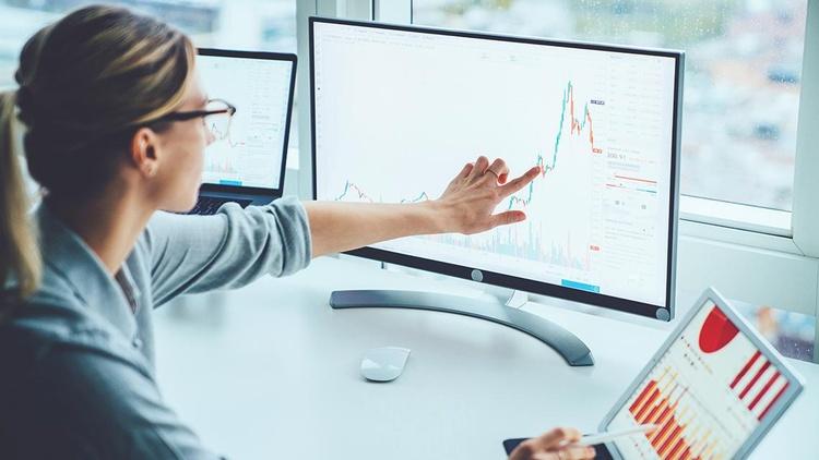Frau zeigt auf Diagramme am Bildschirm