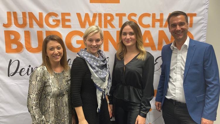 Vier Personen in Kamera blickend vor Junge-Wirtschaft-Banner