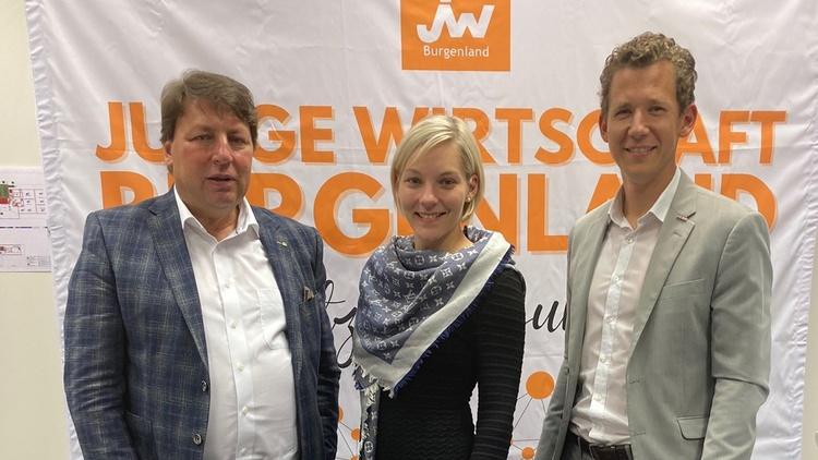 Drei Personen in Kamera blickend vor Junge-Wirtschaft-Banner