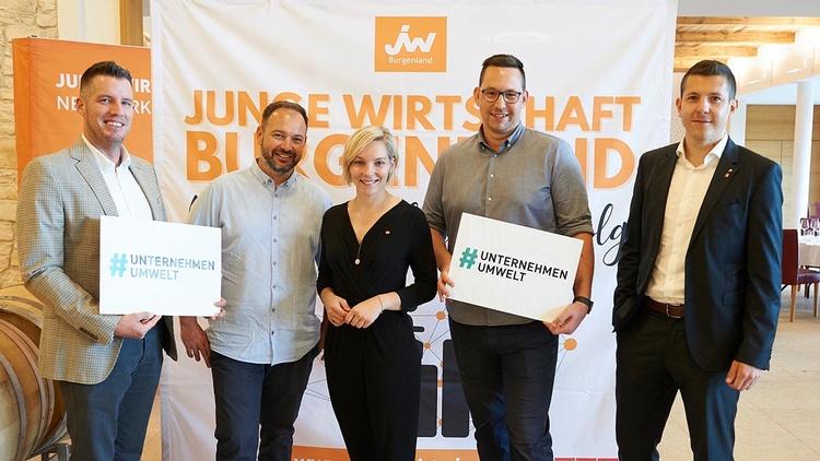 fünf Personen - zwei halten ein Schild mit dem Hashtag Unternehmen Umwelt