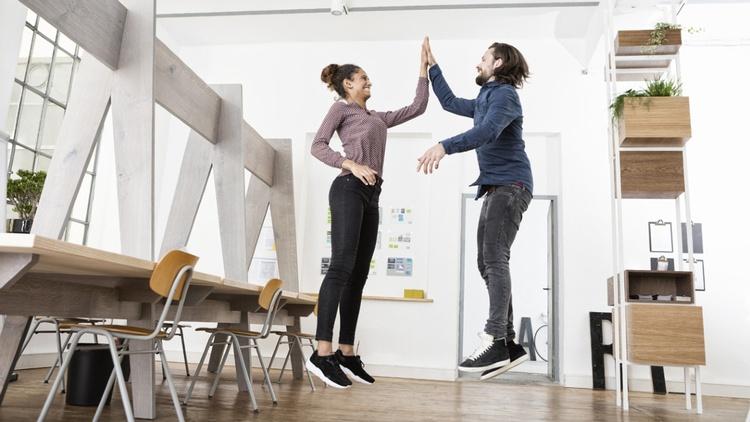 Zwei Personen springen in die Luft mit High-Five