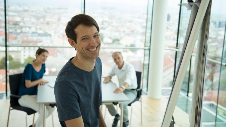 Ein Mann präsentiert etwas an einem Flipchart, im Hintergrund sitzen zwei Zuschauer.