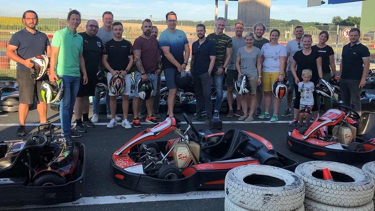 Gruppe Menschen vor Kart-Race-Autos